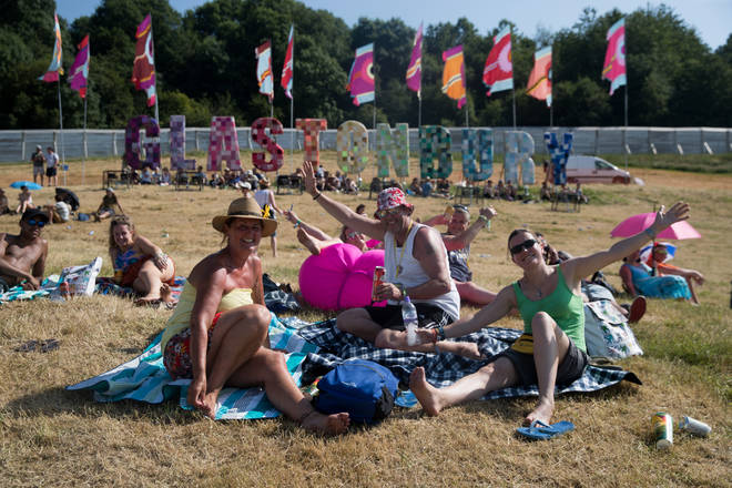 Glastonbury Festival revellers sit outside the sign on Worthy Farm