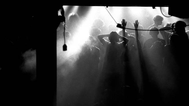 A clubber raises their hands on an atmospheric main stage during a break in the music at the Hacienda, Manchester 1988.