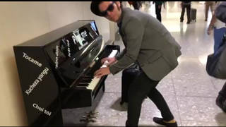 Gaz Coombes plays on a piano at Heathrow airport