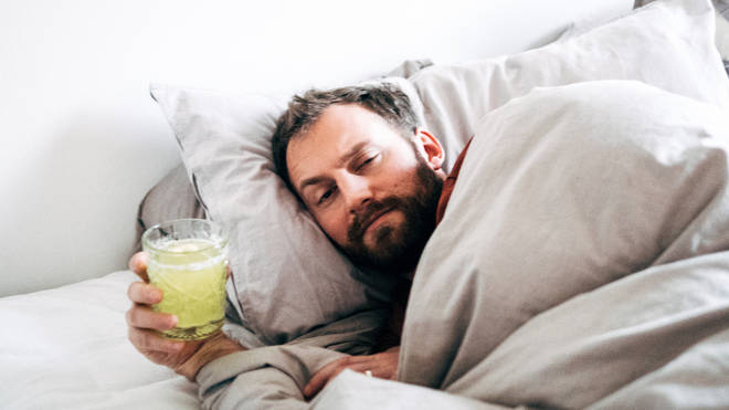 Man holding a drink while lying in bed at home