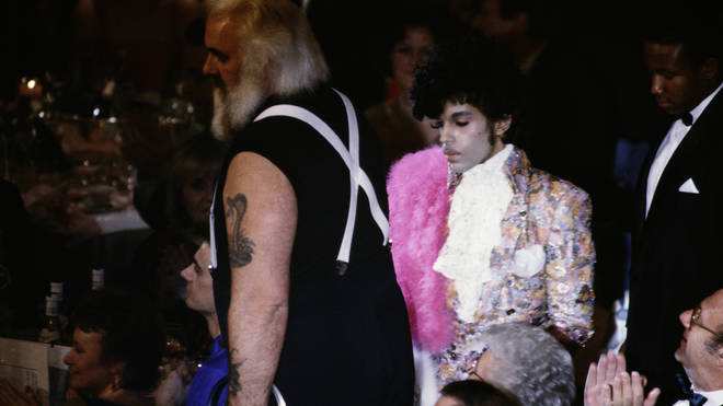 Prince makes his way to collect his 1985 Best International Artist award, accompanied by his ENORMOUS bodyguard Big Chick Huntsberry.