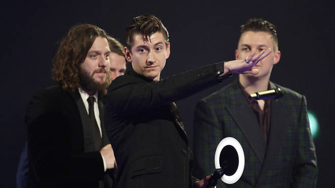 Alex Turner of the Arctic Monkeys on stage after winning Best British Group during the 2014 Brit Awards