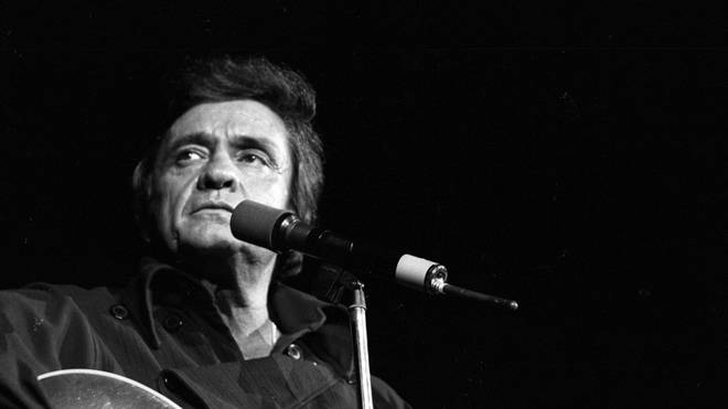 Country singer/songwriter Johnny Cash plays acoustic guitar as he performs onstage at the Anaheim Convention Center on March 11, 1978