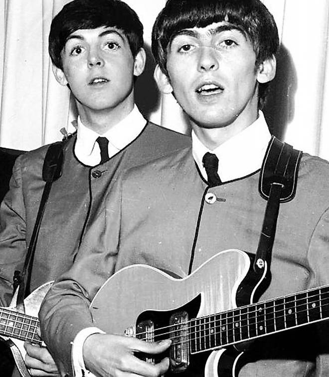 The Beatles' Paul McCartney and George Harrison holding guitar up for auction