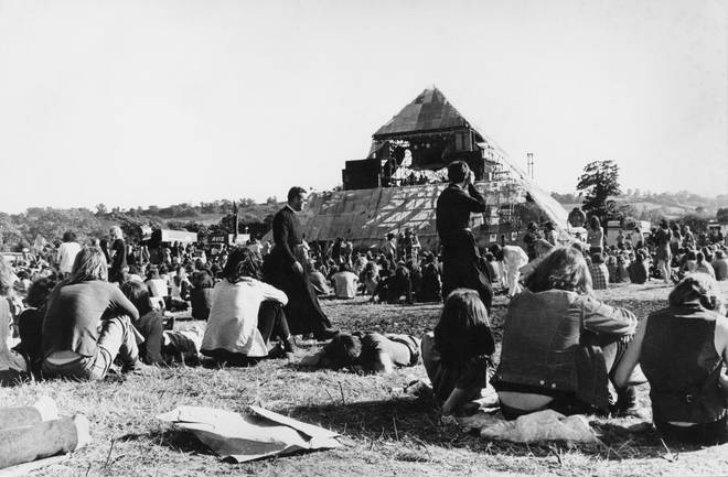Two priests walking amonmg the crowds of festival-goers pictured from behind looking toward the Pyramid stage at the Glastonbury Festival, at Worthy Farm near Glastonbury in Somerset, England, United Kingdom, in June 1971