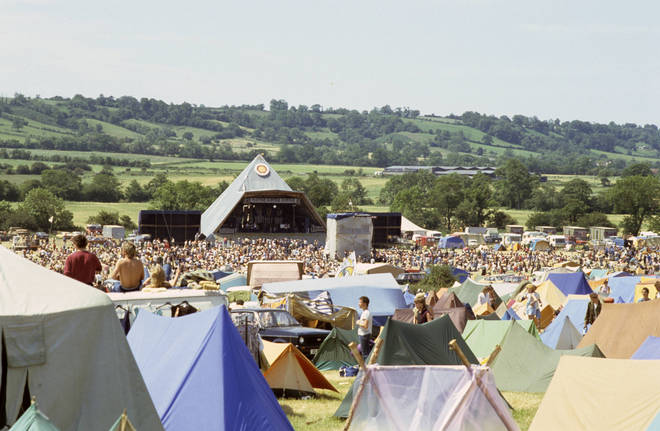 A general view of crowds in front of the original Pyramid stage at Glastonbury Festival in 1983, the campsite can be seen in the foreground