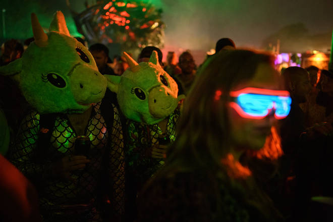 Two festival-goers in costume look on as a woman dances in the early hours of day five of Glastonbury Festival at Worthy Farm, Pilton on June 30, 2019