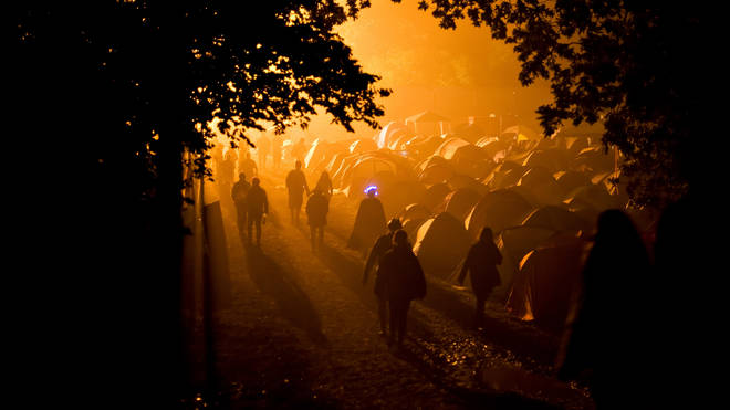 Revellers walk through a camping area in the early hours of the second day of the annual Glastonbury festival near Glastonbury on June 27, 2009