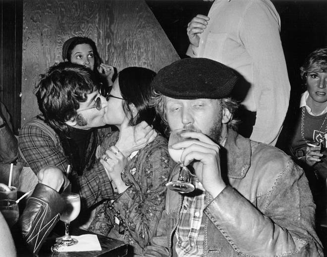 John Lennon kisses girlfriend May Pang as Harry Nilsson quaffs another Brandy Alexander during a night out in Hollywood, March 1974