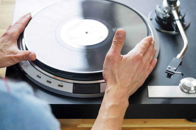 Hands placing vinyl on turntable