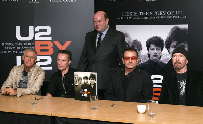 Adam Clayton, Larry Mullen Jr., longtime U2 manager Paul McGuinness, Bono and The Edge sign their book in 2006