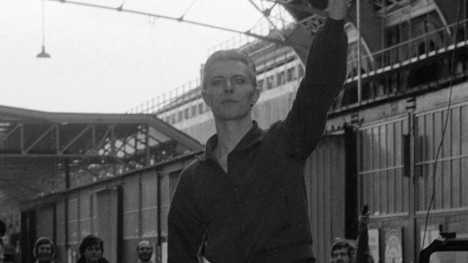 David Bowie waves to fans as he arrives at Victoria Station May 1976