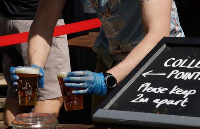 A member of bar staff serves takeaway beer during the coronavirus lockdown measures in South London
