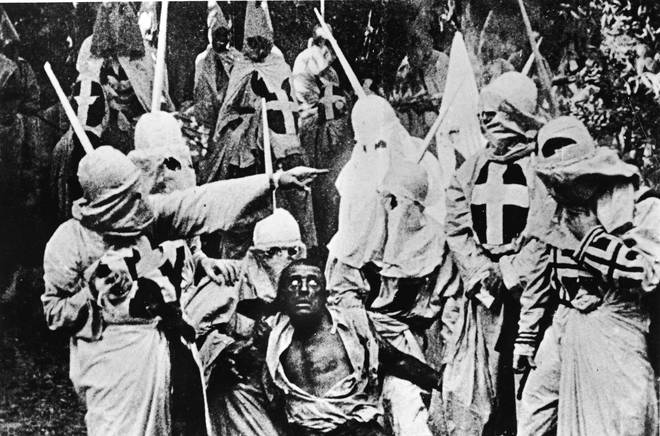 Actors costumed in the full regalia of The Ku Klux Klan surround a white actor in blackface in The Birth Of A Nation