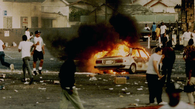 A car burns as looters take to the streets at the intersection of Florence and Normandie Avenues, April 29, 1992.