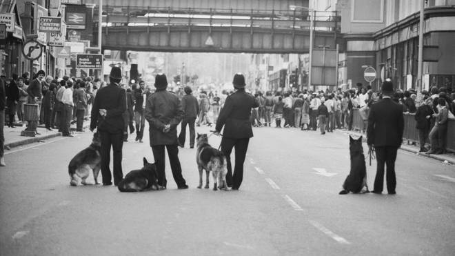 Police dog handlers on Atlantic Road on the second day of riots in Brixton, South London, 13th April 1981. (