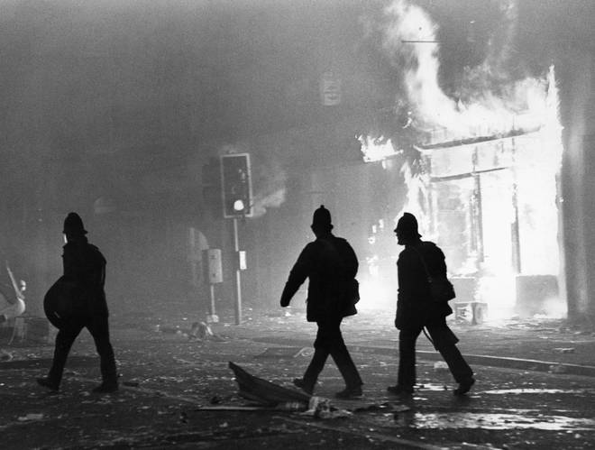 Toxteth Riot 6th July 1981 Police officers in riot gear outside a burning looted shop in Park Road.