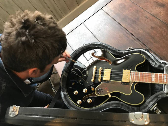 Noel Gallagher signs the guitar