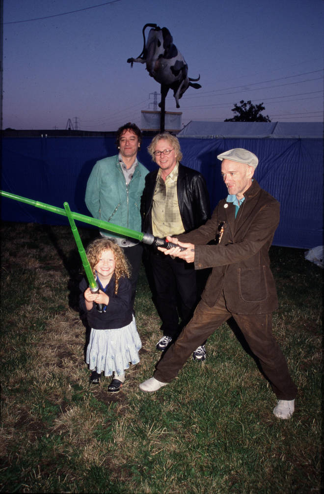 Michael Stipe takes on a small child in a light saber battle while Mike Mills and Peter Buck look on