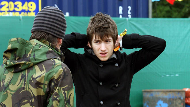 Alex Turner adjusts his collar before hitting the Pyramid Stage for a headline set in 2007