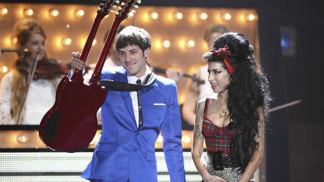 Mark Ronson performing on stage with Amy Winehouse at the BRIT Awards 2008