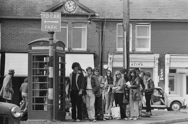 Festival-goers queuing up to make phone calls outside a red telephone box on the Isle of Wight while attending the Isle of Wight Festival, UK, 26th-31st August 1970