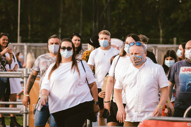 Fans enter the arena with face masks on