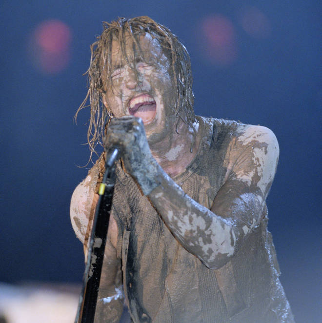 A muddy Trent Reznor performing with Nine Inch Nails on day 2 of Woodstock 94