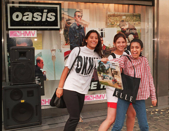 Happy Oasis fans pose with a Be Here Now vinyl on 21 August 1997