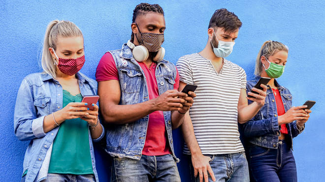 Group of people using their smartphones in covid 19 times protected with face mask