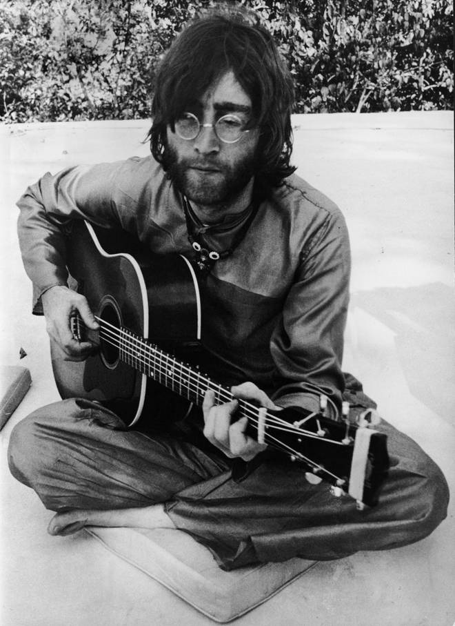 John Lennon playing the guitar in Rishikesh, India in the Spring of 1968