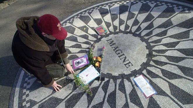A woman lays flowers at the Imagine memorial in Central Park, opposite John Lennon's New York home at the Dakota