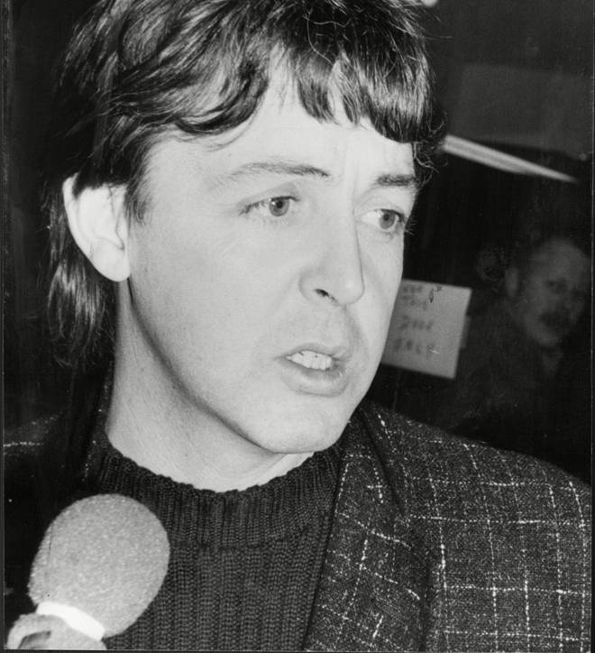 A visibly distraught Paul McCartney is papped as he leaves a recording studio on London's Oxford Street after learning of John Lennon's death