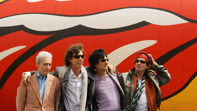 Charlie Watts, Mick Jagger, Ronnie Wood and Keith Richards of the Rolling Stones pose after arriving in front of a blimp with a Rolling Stones logo, at Van Cortland Park in the Bronx section of New York City, May 2002.