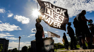 A woman holds a Black Lives Matter flag during an event in remembrance of George Floyd, 24 May 2021