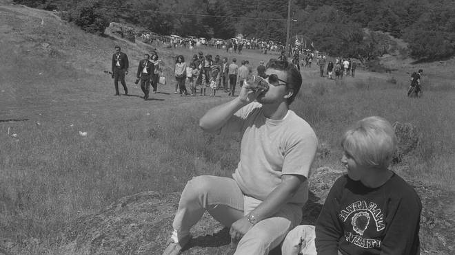 Man chugs beer at festival; partner looks on disapprovingly. A scene to be repeated at rock festivals for the next half century and beyond. Sir, we salute you.