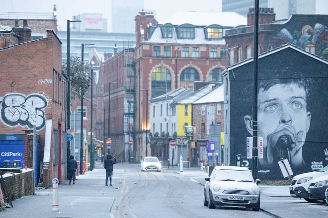 A mural of Joy Division's Ian Curtis watches over the Northern Quarter in Manchester city centre, December 2020