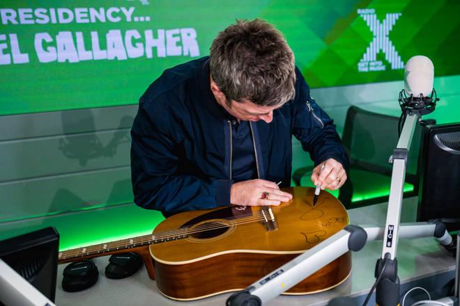 Noel signs the guitar in the Radio X studio