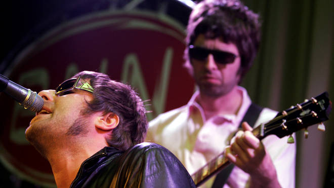 Noel and Liam Gallagher on stage together in Oasis. (Photo by Paul Bergen/Redferns)