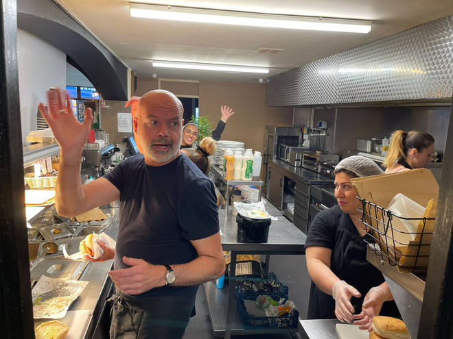 Dom hands out free sandwiches at Essy's cafe in Manchester