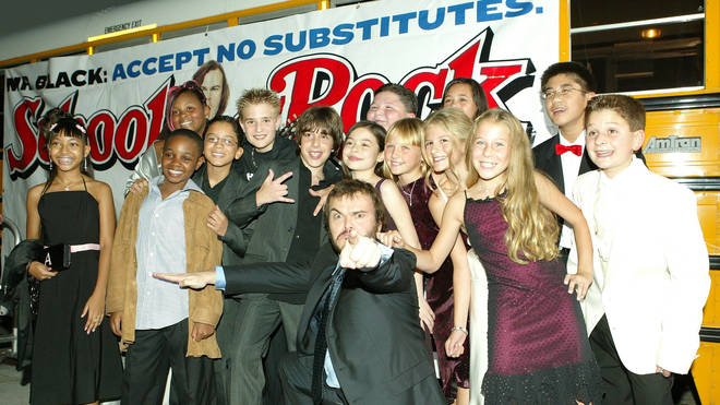 Jack Black poses with children from the cast of School Of Rock at the premiere in 2003