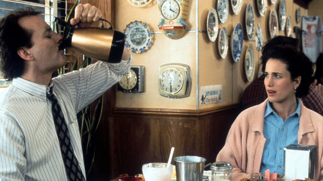 Bill Murray puts down a pitcher of coffee with Andie MacDowell in a scene from the film Groundhog Day, 1993