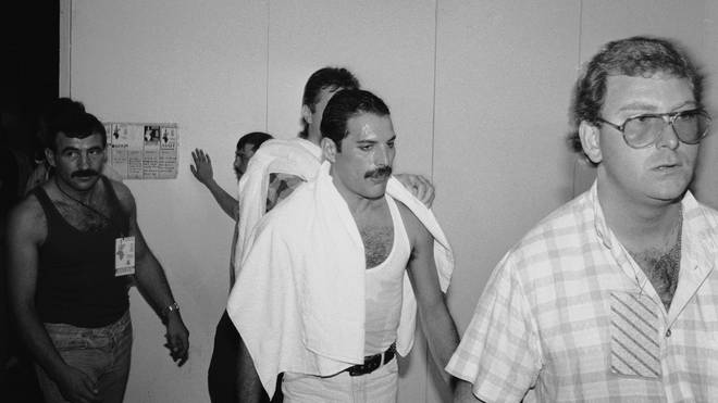 Freddie Mercury backstage at the Live Aid concert at Wembley, 13th July 1985. On the left is his partner Jim Hutton.