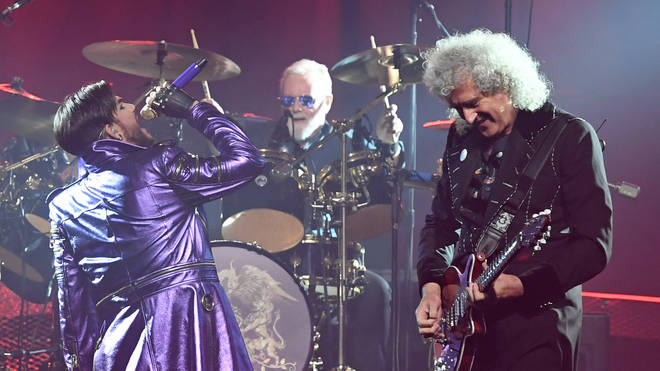 Adam Lambert sings with Queen drummer Roger Taylor and guitarist Brian May