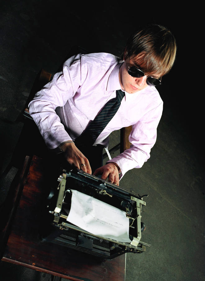 Paul Banks of Interpol poses for a portrait wearing sunglasses and typing at a typewriter on October 29, 2002 in Los Angeles, California.