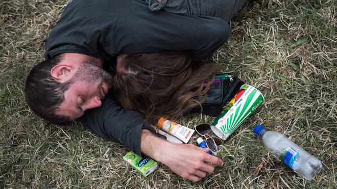 A couple fall asleep on the grass at Glastonbury Festival 2017