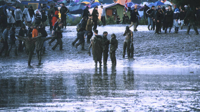 A general view of festival-goers covered in mud at a rain-soaked Glastonbury Festival, United Kingdom, 1997