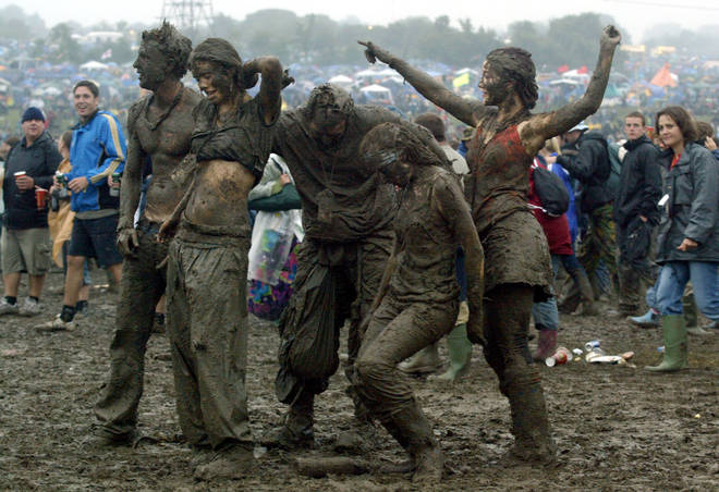 Festival-goers dance in the mud in front of the Pyramid stage at Worthy Farm, Pilton, Somerset, at the 2004 Glastonbury Festival