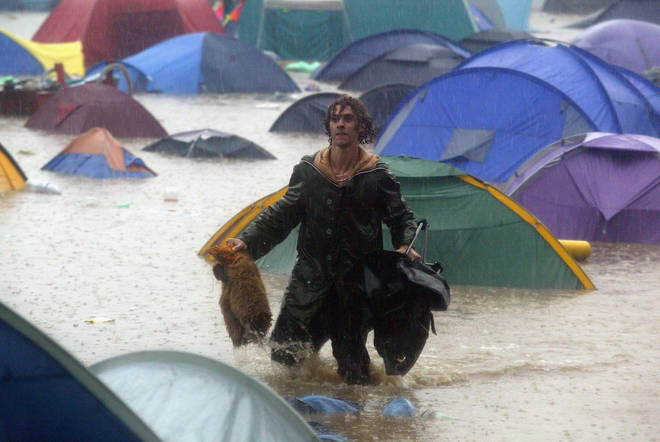 A festival-goer tries to rescue belongings washed away on the first day of the Glastonbury Music Festival 2005