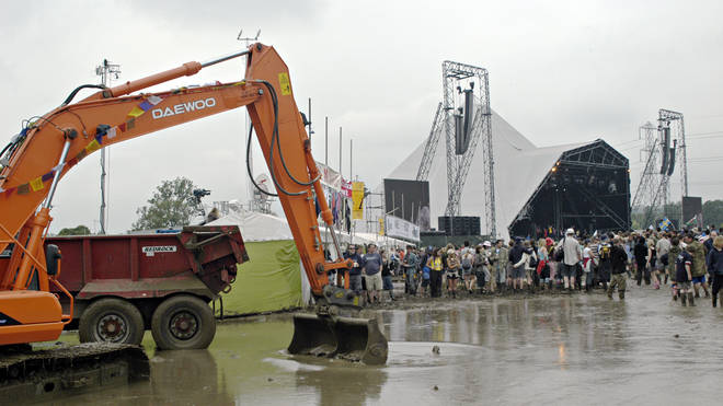 Excavators valiantly try and improve conditions in front of the Pyramid Stage at Glastonbury, 2007.